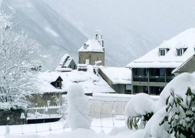 Vue depuis la terrasse de l'appartement en hiver avec le village enneigé face à la location