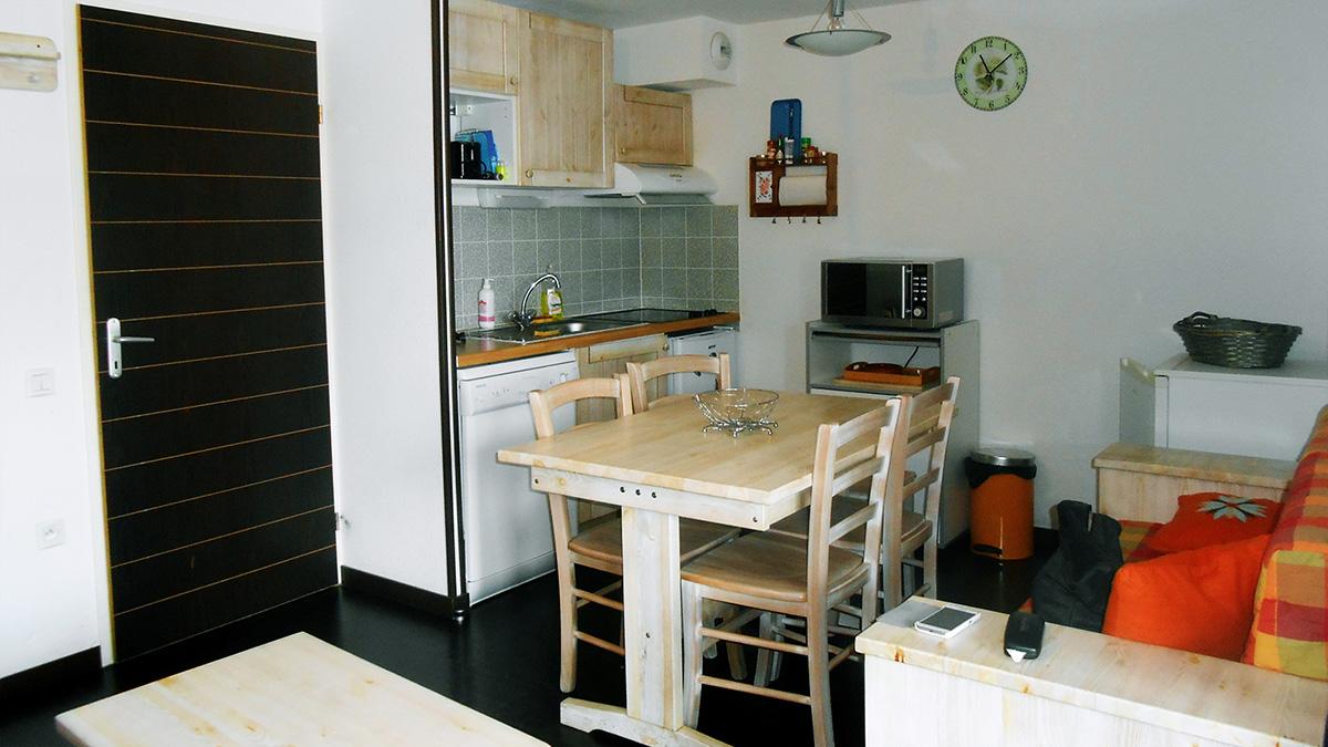 Intérieur de l'appartement avec le coin salon, la cuisine et l'accès à la chambre secondaire de la location