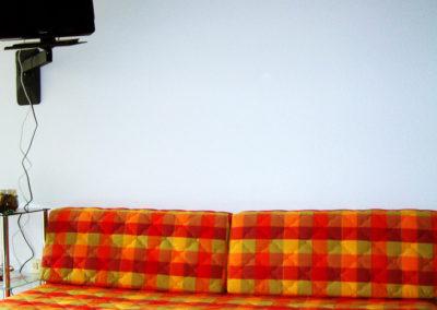 Coin salon avec canapé convertible en lit deux places, télévision et lecteur DVD