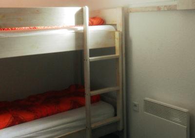 Chambre secondaire avec lits superposés sous la fenêtre