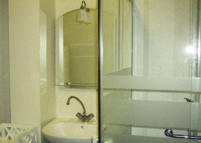 Salle d'eaux de l'appartement avec douche à l'italienne, lavabo, miroir, lave-linge et WC