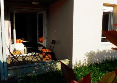 Terrasse extérieure de la location avec table et chaises, vue de l'entrée de l'appartement et de la fenêtre donnant sur la chambre principale